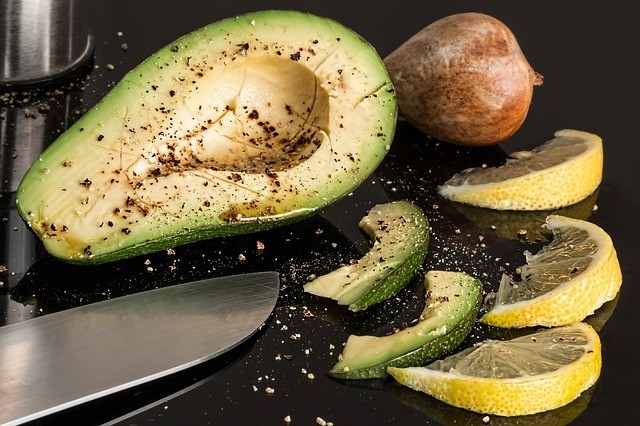 Seasoned and sliced avocado next to knife and lemon slices