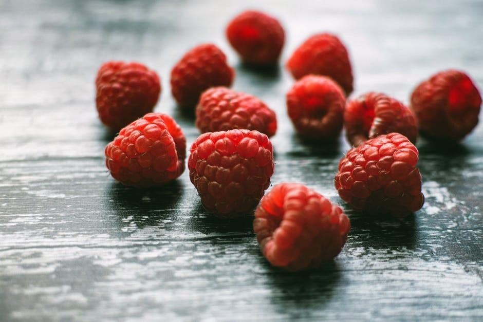 A handful of raspberries on a wooden table