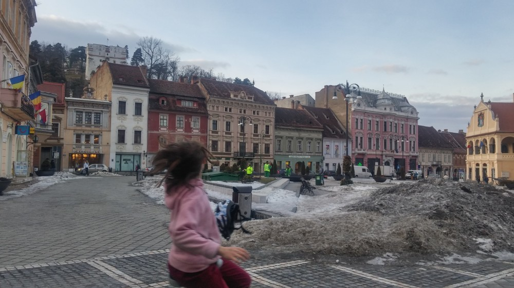 Child unicycles across a snowy town square