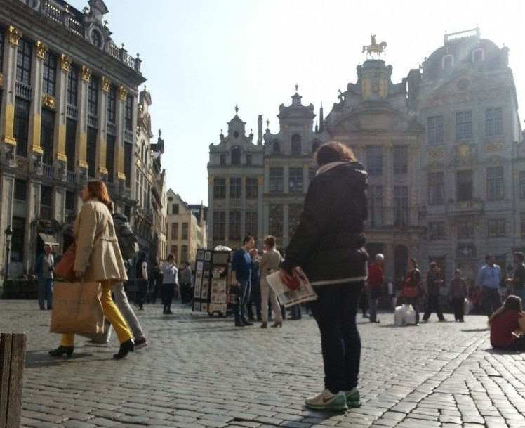 Woman standing in centre of image of Brussels Grand Place