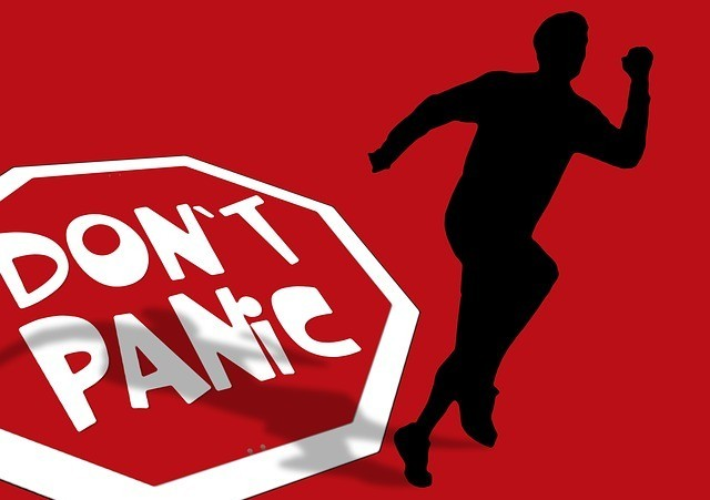 A sign saying 'don't panic' and a man seen running away