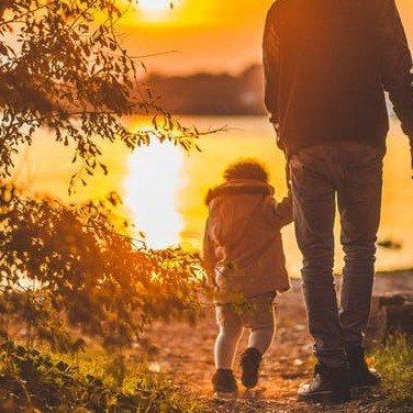 The back of a father holding a child's hand and walking towards a water with the sun being reflected in it