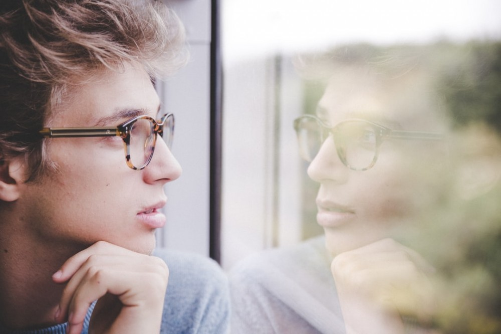 A man with glasses seeing his own reflection in a window