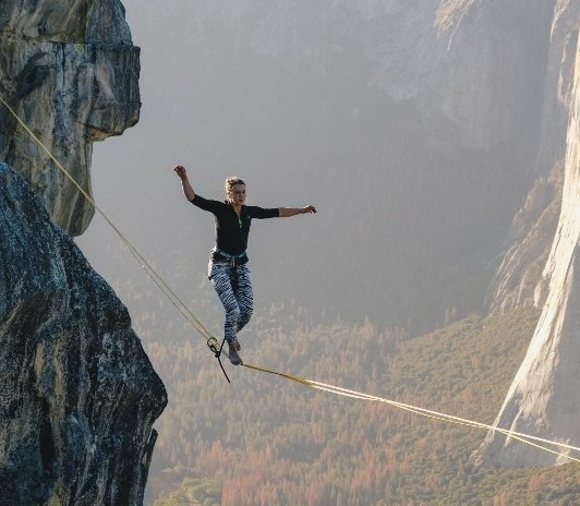 Image of woman walking on a tightrope.