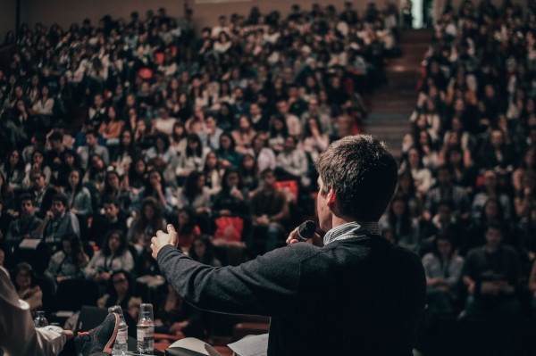 Man with microphone speaking to an audience. Photo by Miguel Henriques on Unsplash