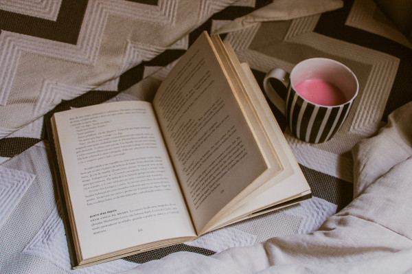 Picture of book open next to a mug