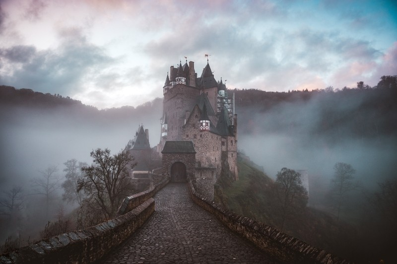 Image of castle in the middle of a foggy land.