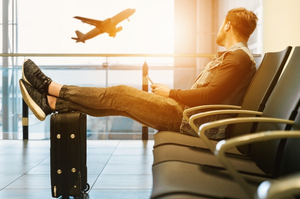 Man sitting in airport chair looking at plane flying outside. Photo by JESHOOTS.COM on Unsplash