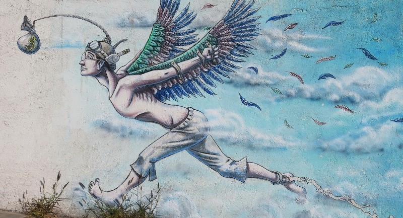 Painting of shirtless man wearing a hat, fake birds' wings with feathers flying out, and pants.