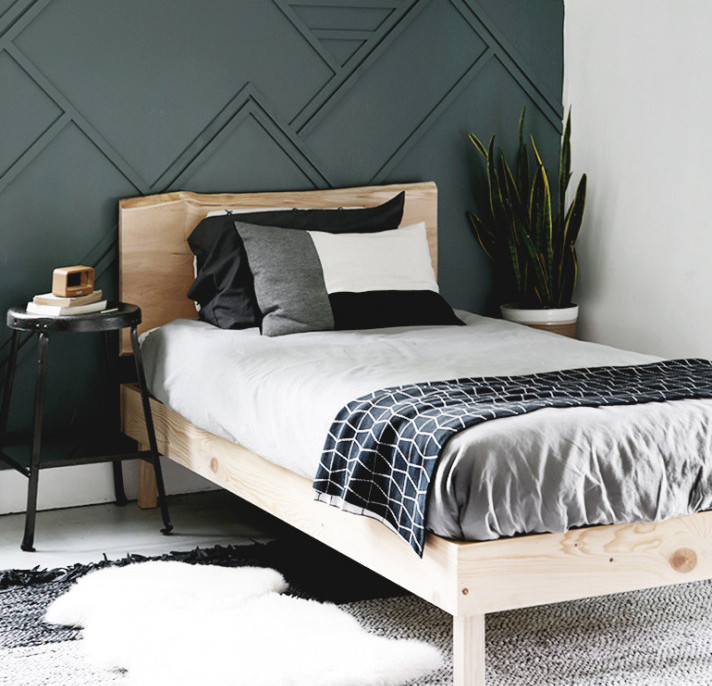 DIY Live Edge Wood Platform Bed Paired with green accent wall and decorated with comfy area rug and indoor plant to make a cozy bedroom design