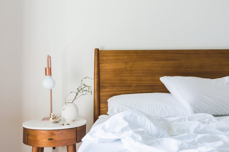 Simple Platform Bed Plans: Wooden platform bed layered in crisp white sheets and matching white side table with wooden base
