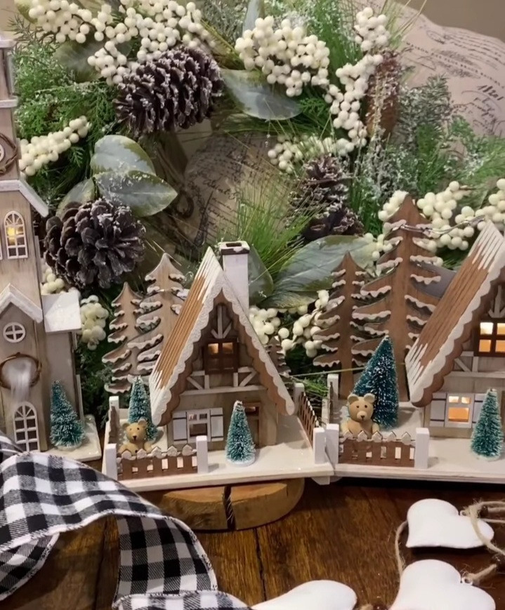 Miniature toy houses covered in snow and decorated with Christmas lights, trees, and pinecones to create the perfect holiday display