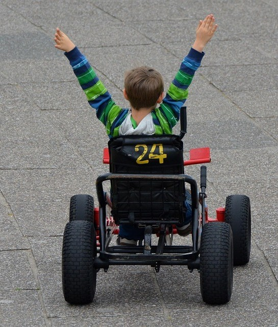 child with arms raised after winning a car race
