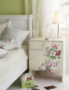 Decoupage nightstand used in the decor of a shabby chic bedroom.