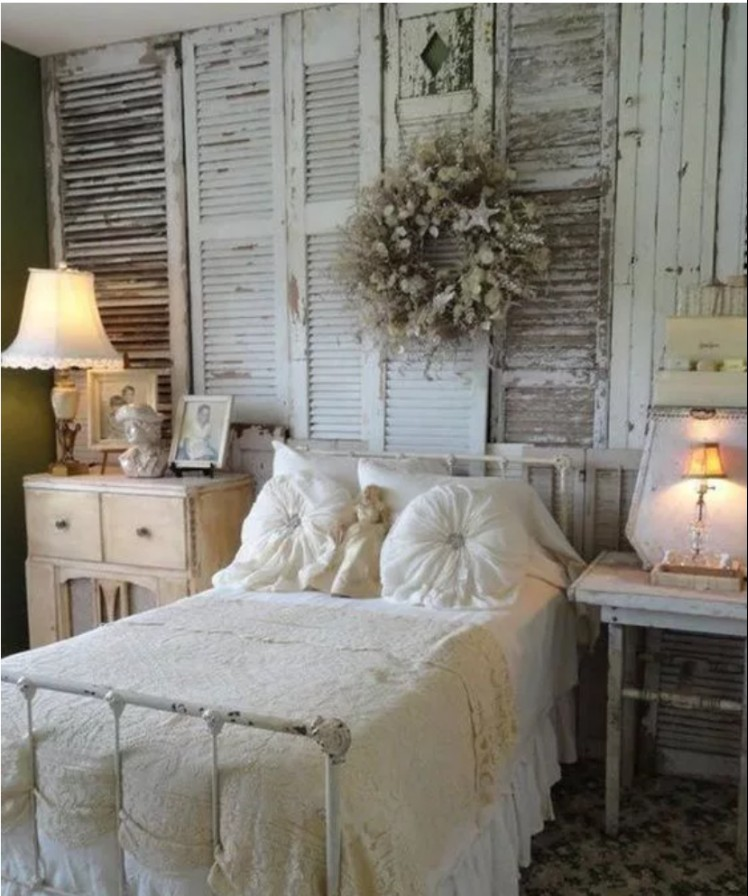 Shutter covered wall in a shabby chic bedroom makes a statement.