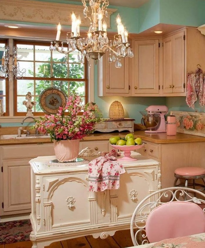 Shabby chic kitchen with light pink cabinets, pale blue walls, painted cabinet on legs for an island, and a chandelier for lighting.
