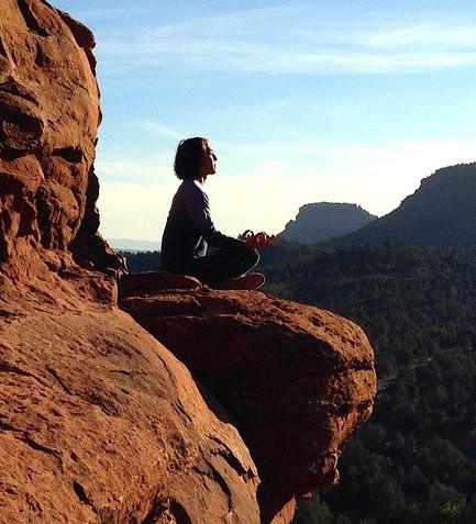 Lady meditating on cliff