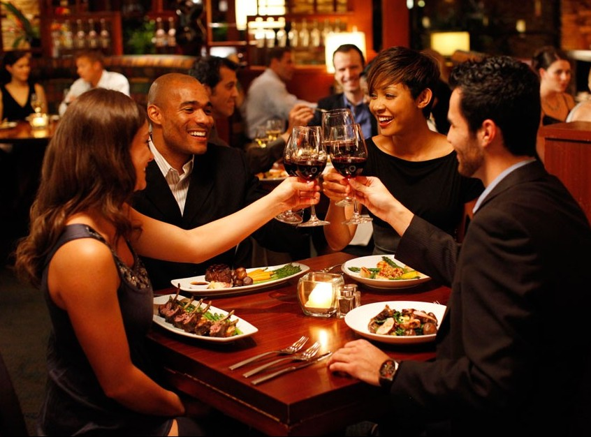 people sitting at tables in a restaurant toasting
