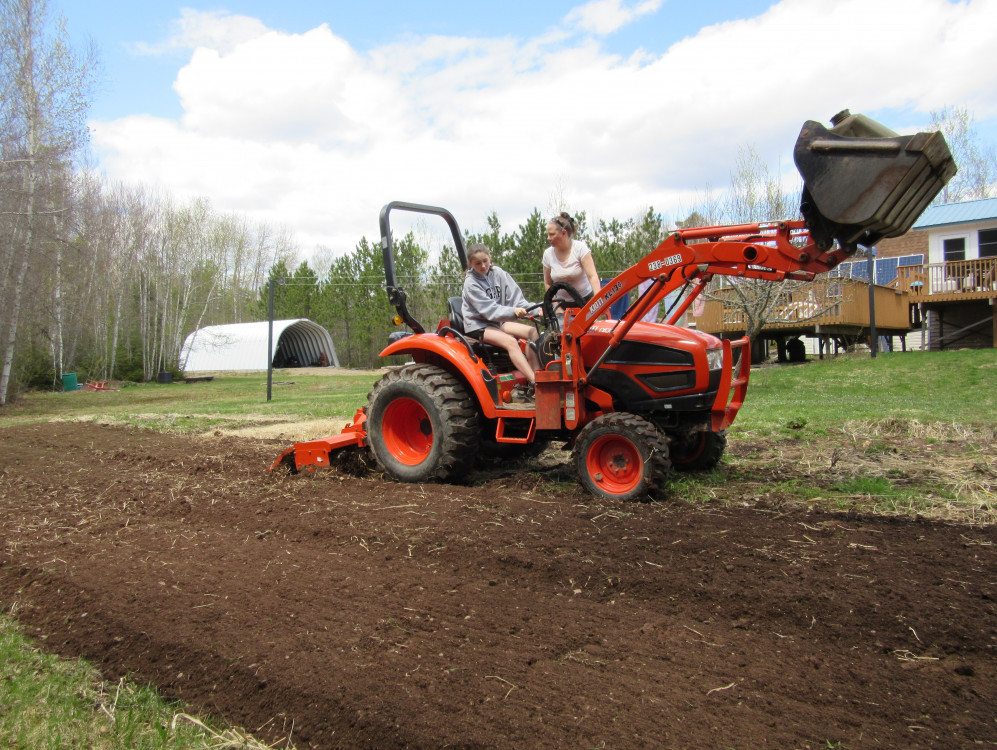 Vegetable Gardening In Canada - oldest granddaughter driving with me supervising tilling the garden