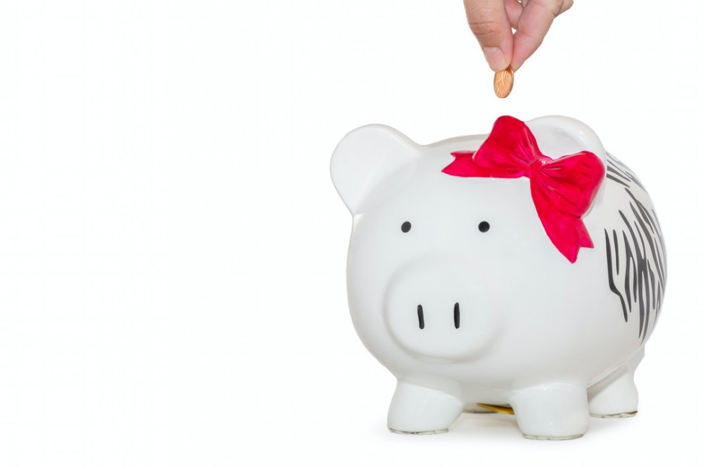 What Is The Meaning Of Wealth? - dropping penny in piggy bank