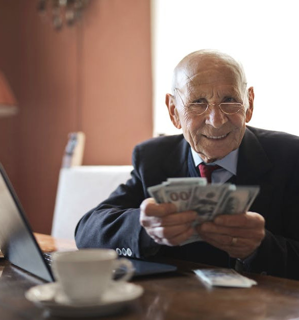The Cash Money Sites - elder man making money from laptop