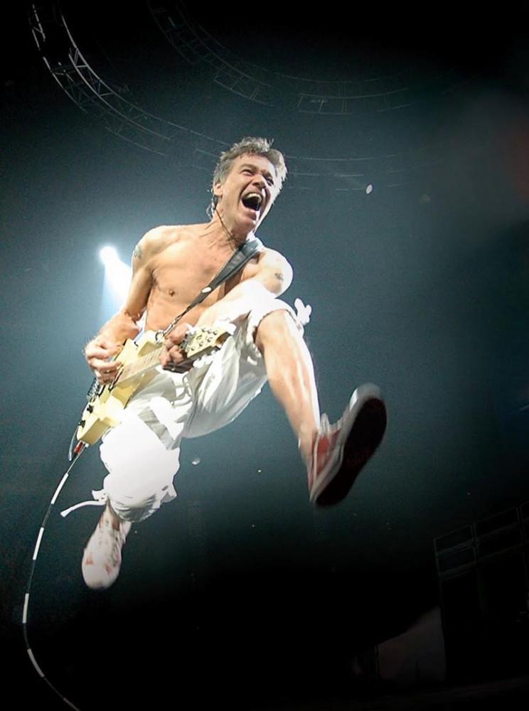 Eddie Van Halen leaping in the air, playing an EVH Wolfgang guitar