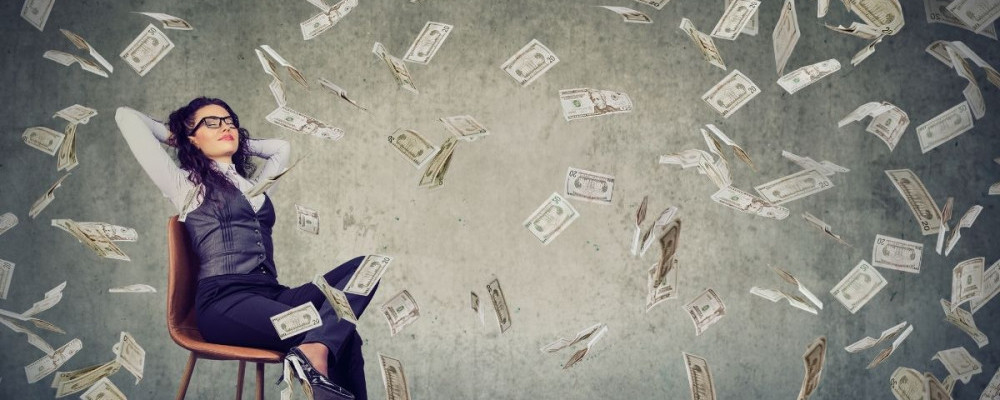 Woman sitting on a chair. Money flying all around her.