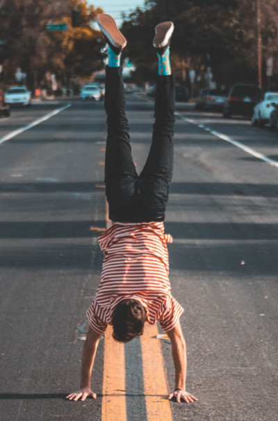 Man standing on hands in the middle of a street