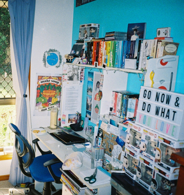 Bookshelf-containing-books-above-a-desk-with-a-laptop-and a-blue-chair-infront