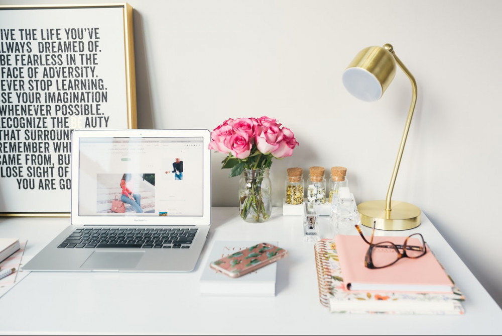 Desk-With-A-laptop-mobile-phone-lamp-flowers-a-pair-of-glasses-note-books