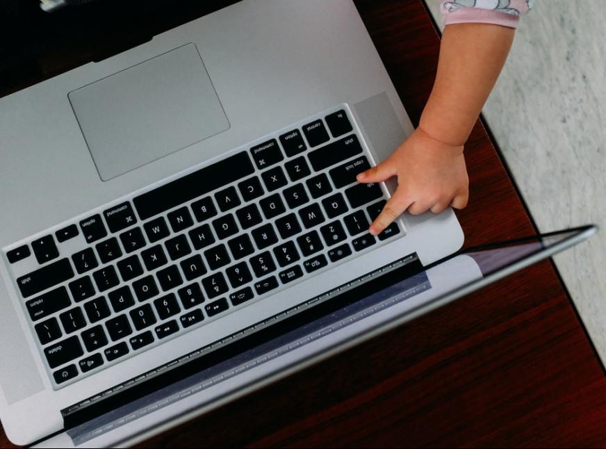 child-pressing-a-key-on-a-laptop-