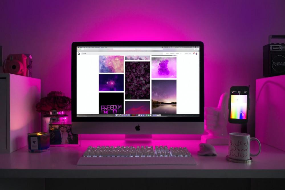 Apple-Mac-computer-on-a-desk-back-lit-with-a-purple-bulb