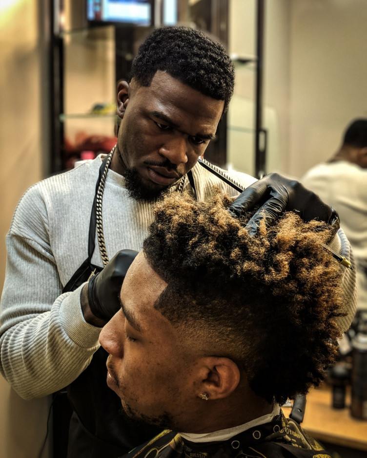 A male Hair Professional attends to another man's hair