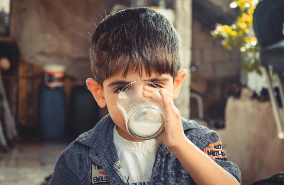 A child drinking milk from a glass