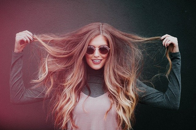 A woman happily holding up and showing off her healthy hair.