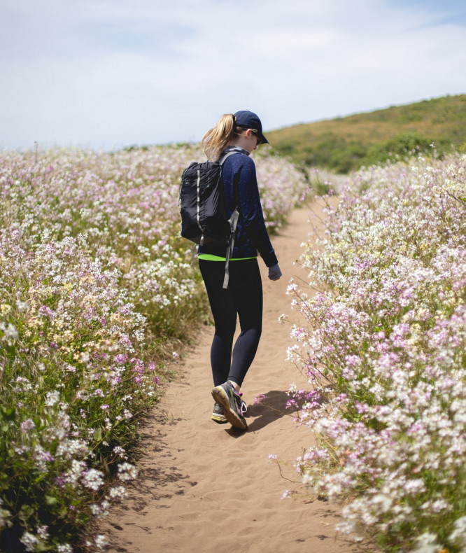 A woman walking along a path surrounded by flowers