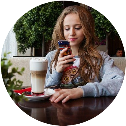 A woman looking at her phone with a milky coffee on the table in front of her