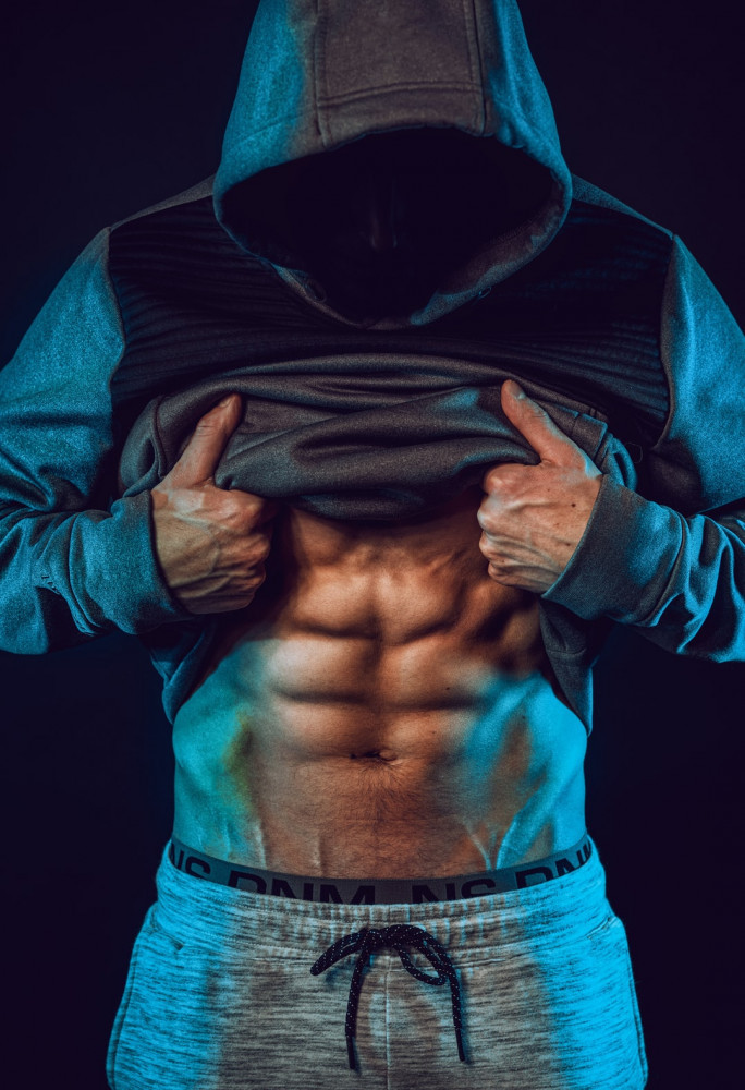 A man lifting his top to reveal 6-pack abs