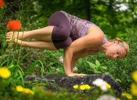 A woman performing the side crow exercise