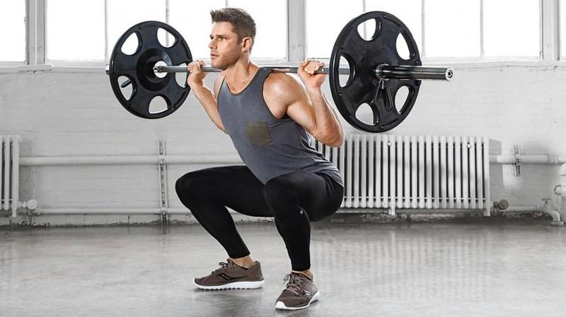 A man performing a barbell squat