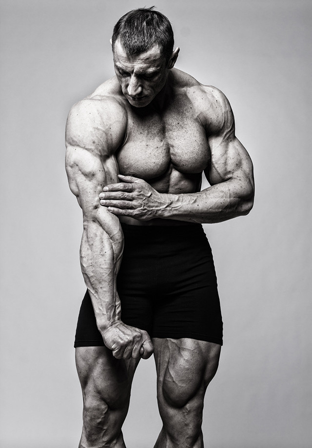 A muscular man with his hand against his tricep