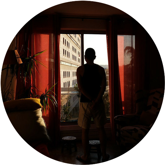 A man standing in a darkened room looking out a window
