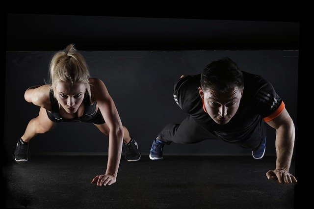 A man and a woman performing one-handed push ups