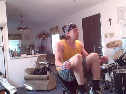 A man sitting in his front room on an exercise machine with pulleys
