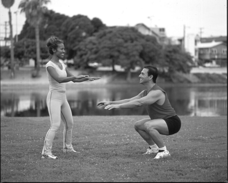 A man performing bodyweight squats while a woman looks on