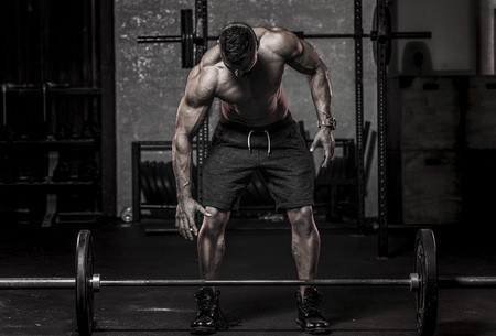 A Muscular Man Preparing to Lift a Barbell