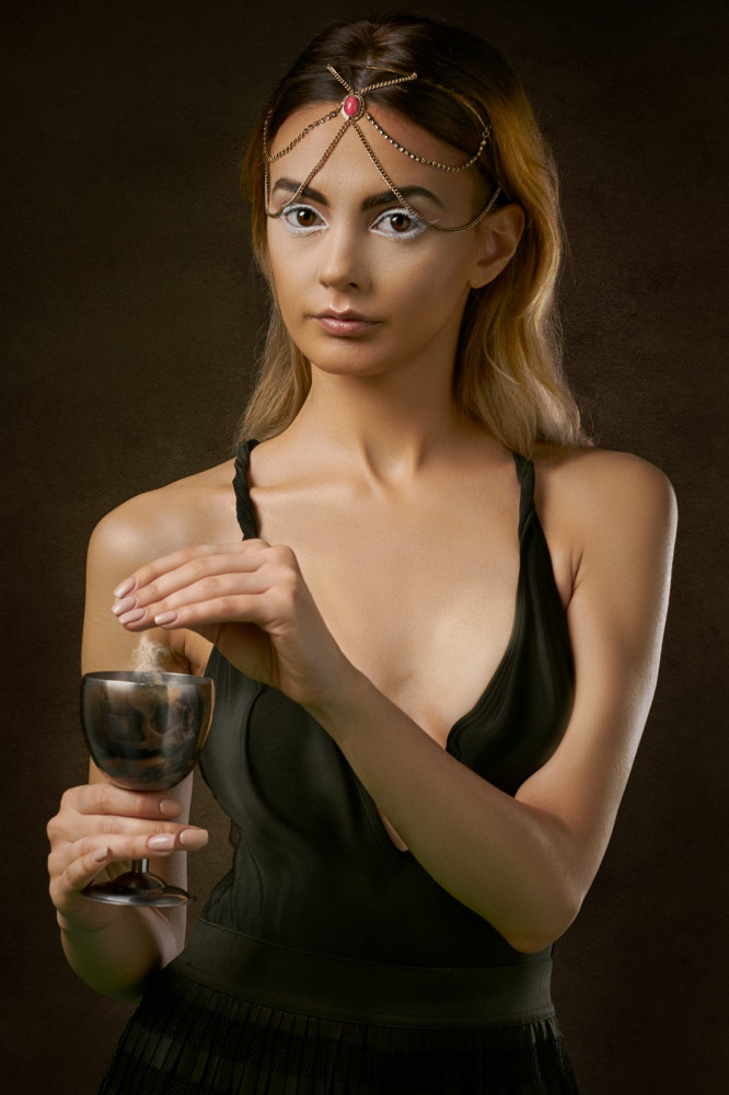 A woman wearing a black dress and costume jewelry around her head, holding a wine glass