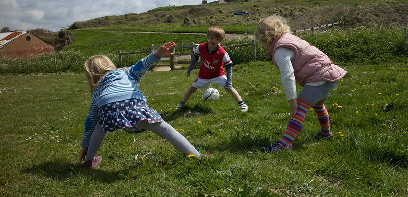 Three Children in a Field Stretching
