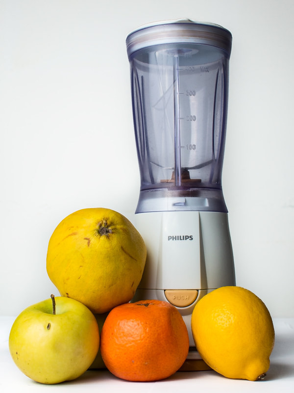 A blender and some oranges and lemons