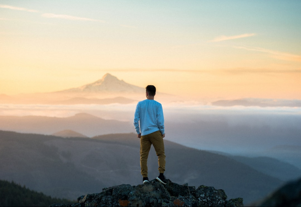 A Man Standing On a Mountain Top Looking Across the Horizon at Other Mountains and the Sky